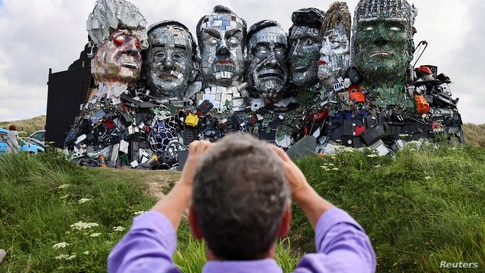"""A man photographs """"Mount Recyclemore"""", an artwork depicting the G7 leaders looking towards Carbis Bay, made from electronic…"""