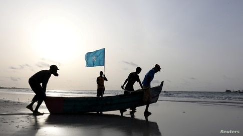 Fishermen carry a boat in to the water in Lido beach, Mogadishu's Abdiaziz District, Somalia June 18, 2021. REUTERS/Feisal Omar…