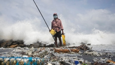 Sri Lankan man, Kindston Jayalath fishes on a polluted beach filled with plastic pellets washed ashore from the fire-damaged…