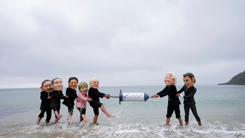 Activists wearing giant heads of the G7 leaders tussle over a giant COVID-19 vaccine syringe during an action of NGO's on…