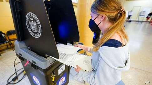 June Harkrider, who turned 18 in March, places her ballot in the scanner as she votes for the first time during early voting in…