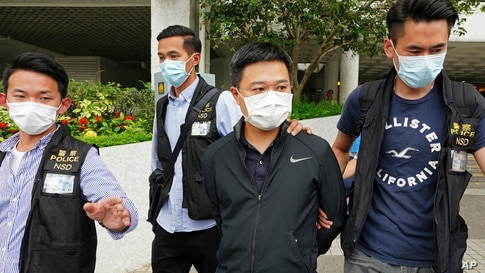 Ryan Law, second from right, Apple Daily's chief editor, is arrested by police officers in Hong Kong, June 17, 2021.
