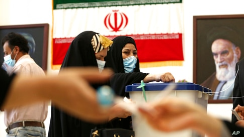 An Iranian woman casts her vote during the presidential election at a polling station inside the Iranian consulate in Karbala,…