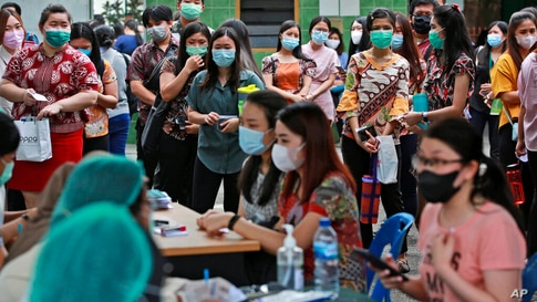 People line up as they wait for their turn to get a shot of the Sinovac COVID-19 vaccine during a mass vaccination at Putri…