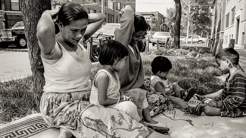 Cambodian women and children relax and play between the street and sidewalk outside their apartment building in the 1990s along W. Argyle Street in the Uptown neighborhood of Chicago. (Photo: Stuart Isett)