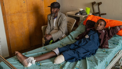 A boy, accompanied by his father, recovers from an amputation in the Ayder Referral Hospital on June 4, 2021, in Mekelle, Ethiopia. He lost his lower leg after being hit by artillery fire. (VOA/Yan Boechat)