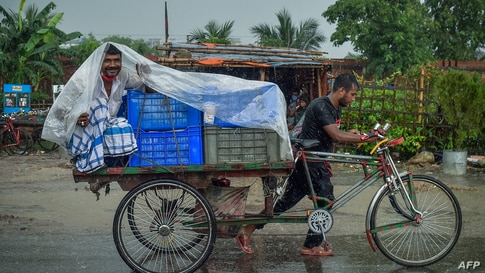 A man wraps a plastic sheet to shelter from the rain while sitting on a cycle-rickshaw cart in Dhaka, Banglaesh.