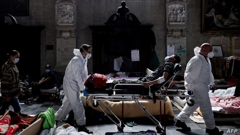 Nurses evacuate a migrant who is on a hunger strike to the hospital from Saint-Jean-Baptiste-au-Beguinage church in Brussels, Belgium.