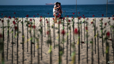 People hug behind roses placed by the NGO Rio de Paz on Copacabana beach, Rio de Janeiro, in memory of Brazil's half a million COVID-19 victims.