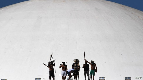Brazilian Indigenous from different tribes protest against a bill that is being discussed in the Deputies Chamber that changes the rules of the indigenous territories demarcation, at the top of of the National Congress building in Brasilia, on June 8, 2021.