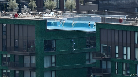 People swim in the Sky Pool - a transparent acrylic swimming pool bridge between two apartment blocks - at Embassy Gardens in south-west London as the city enjoys another sunny day.