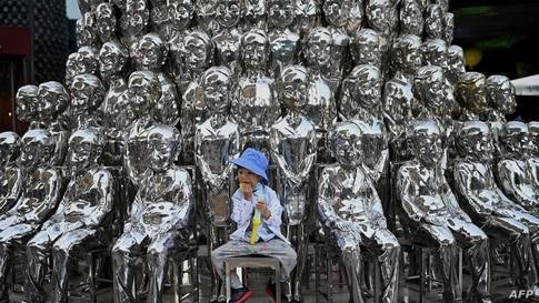 A boy sits on a chair amongst sculptures on display at a shopping center on International Children's Day in Beijing. China announced it would allow couples to have three children.