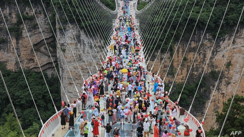 People walk on a glass-bottomed skywalk in Zhangjiajie, in China's central Hunan province, June 20, 2021.