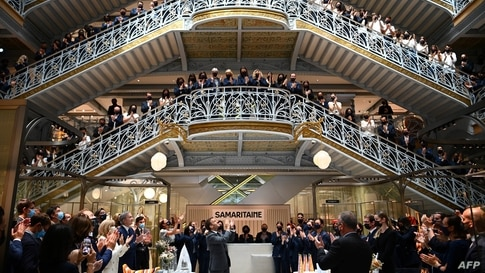 French President Emmanuel Macron (C) and employees of Paris' iconic department store La Samaritaine applaud during a ceremony marking the store's reopening after 16 years of closure.