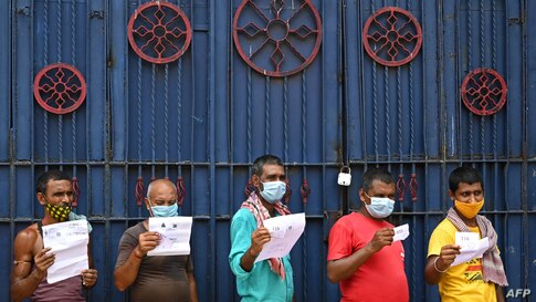 Workers hold documents as they wait for their turn to receive the first dose of Covishield vaccine in a passenger bus converted into a mobile vaccination center in Kolkata, India.