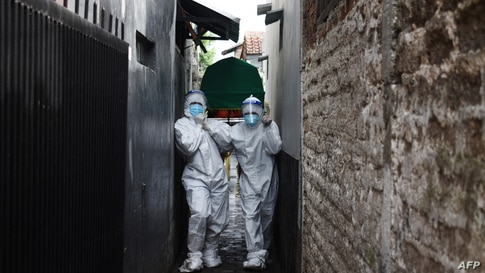Health workers remove the body of a man who died of Covid-19 coronavirus at his Home in Bandung, Indonesia, June 23, 2021.