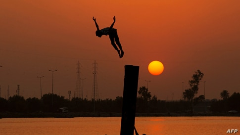 An Iraqi youth swims in the Shatt Al-Arab river by the port of Maqil amid a heat wave in the southern city of Basra, June 29, 2021.