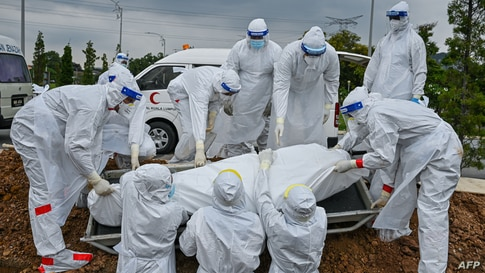 Volunteers wearing protective suits lay down the body of a Covid-19 victim for burial at the Raudhatul Sakinah Muslim cemetery in Kuala Lumpur, Malaysia.