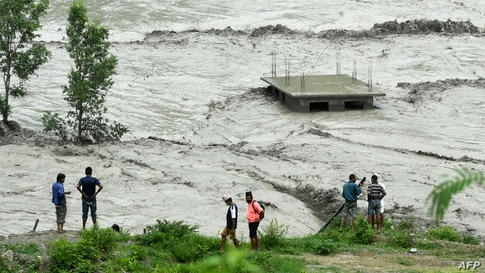 Residents stand along the banks of the overflowed Melamchi River following heavy monsoon rains in Sindhupalchok, some 70 km northeast of Kathmandu, Nepal.