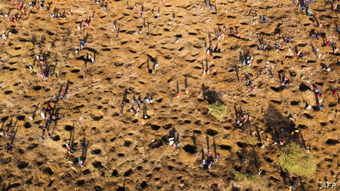 An aerial view shows people digging as they search for what they believe to be diamonds after the discovery of unidentified stones at KwaHlathi village near Ladysmith in KwaZulu Natal, South Africa.