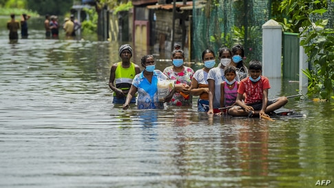 Residents make their way through floodwaters after heavy monsoon rains in Kelaniya, on the outskirts of Colombo, Sri Lanka.