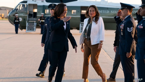 Vice President Kamala Harris, left, with Rep. Veronica Escobar, D-Texas, salutes as they board Air Force Two, June 25.