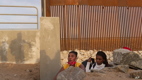A Haitian migrant family looks to emerge from a rocky canal adjacent to a gap in the U.S. border wall in Yuma, Arizona, June 9, 2021.