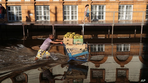 A man pushing a shopping cart loaded with bananas wade through a flooded street in downtown Manaus, Amazonas state, Brazil.