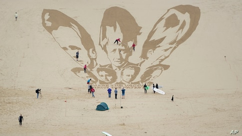 Surfers and sunbathers look on as activists put on the finishing touches as they draw the heads of G7 leaders in the sand on the beach at Newquay, Cornwall, England.