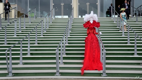 Debora Day in an ornate red outfit poses on the steps for photographers on the third day of the Royal Ascot horserace meeting, which is traditionally known as Ladies Day, at Ascot, England.