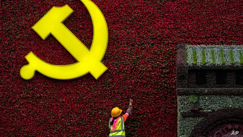 A worker installs a flag-shaped flowers decoration with a Communist Party's logo in Beijing, China.