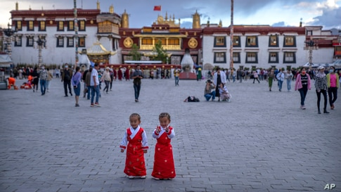 Girls stand on a square in front of the Jokhang Temple in Lhasa in western China's Tibet Autonomous Region.