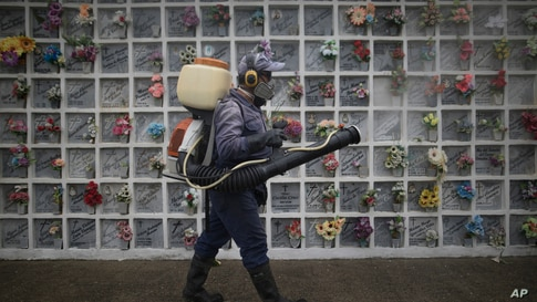 A cemetery worker sprays disinfect at niches inside Nuestra Señora de Belen cemetery amid the COVID-19 pandemic in Fusagasuga, Colombia.