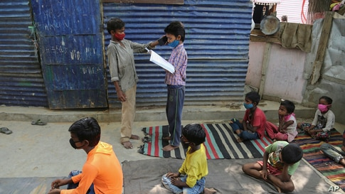 A student holds a mobile phone for another so that a fellow student can listen to instructions from a teacher as children attend online classes at a slum on the outskirts of Jammu, India.