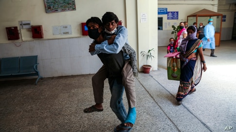A man carries another on his back as he brings him for medical check up at a government hospital in Jammu, India.