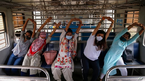 Commuters in a suburban train take part in a yoga session to mark International Yoga Day in Mumbai, India.