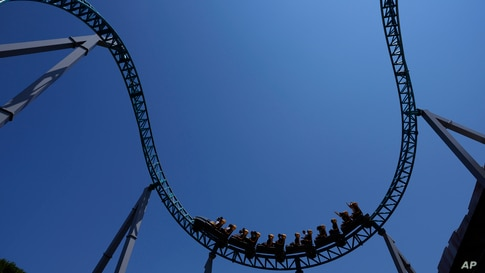 Visitors enjoy a ride on a roller coaster at Cinecitta World amusement park in the outskirts of Rome, Italy, on the day of its reopening.