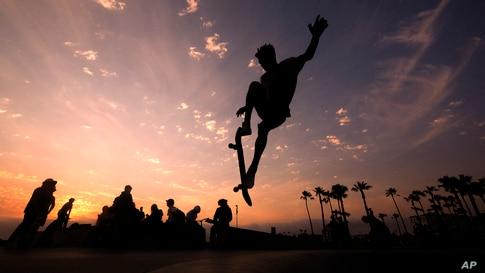 A skateboarder is silhouetted as he jumps high at the skateboard park during sunset, June 16, 2021, in Venice Beach, Los Angeles, California.