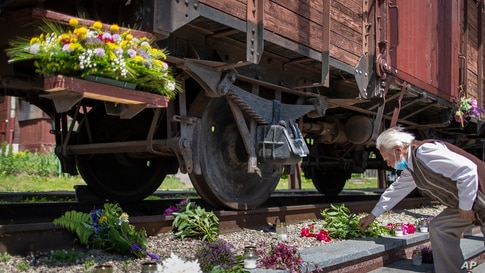 A man lays flowers on rusty railway tracks at the Naujoji Vilnia railway station in Vilnius as Lithuania marks the 80th anniversary of mass deportation by the Soviet Union.