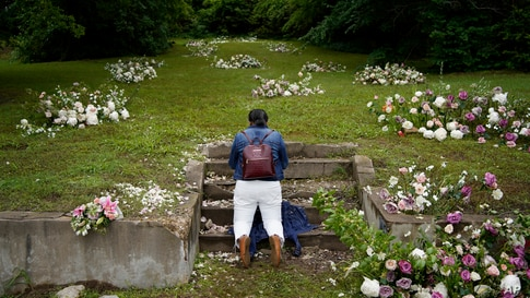 Linda Porter of Birmingham, Ala., kneels at a makeshift memorial of flowers for the Tulsa Race Massacre near the historic Greenwood district during centennial commemorations of the massacre, June 1, 2021, in Tulsa, Oklahoma.