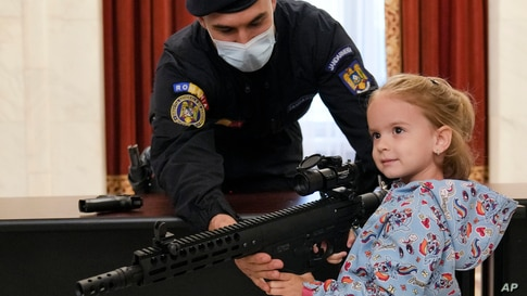 A girl poses with a weapon at a stand set up by Romania's gendarmerie at the Palace of the Parliament, on International Children's Day in Bucharest.