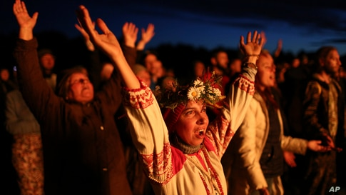 People wearing traditional Russian village-styled clothes, celebrate the summer solstice around a bonfire in Okunevo village, some 200 kilometers (124 miles) northeast from Siberian city of Omsk, June 21, 2021.