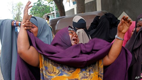 A mother cries after her son was killed in a suicide bomb attack at a military base in Mogadishu, Somalia.