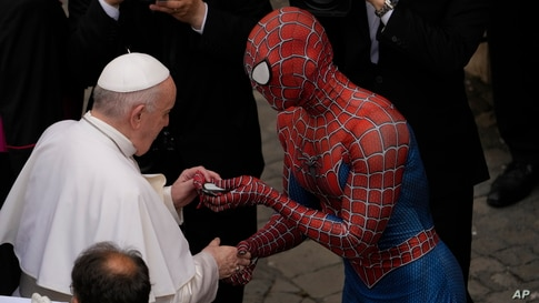 Pope Francis meets Spider-Man, who presents him with his mask, at the end of his weekly general audience with a limited number of faithful in the San Damaso Courtyard at the Vatican.