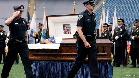 Police officers salute the casket of K-9 Kitt in Gillette Stadium during a memorial service held in honor of the police dog, who was killed during a domestic violence call, in Boston, Massachusetts, June 22, 2021.