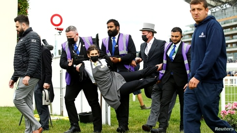 An extinction rebellion protester is escorted from the racecourse during the Royal Ascot horse race in Ascot, England, June 19, 2021.