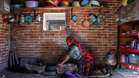 Maria Nieves, an indigenous Zapotec woman, grinds corn at her home in the rural village of San Bartolome Quialana, in Oaxaca state, Mexico, May 31, 2021.