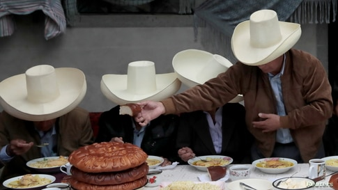 Peru's presidential candidate Pedro Castillo (R) hands over bread during a breakfast with members of his family before casting his vote in Chugur.