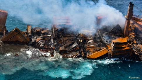 Smoke rises from a fire onboard the MV X-Press Pearl vessel as it sinks while being towed into deep sea off the Colombo Harbor in Sri Lanka.