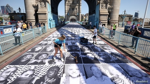 Workers place portraits of Londoners, including London's Mayor Sadiq Khan, by French artist JR, on the road at Tower Bridge to celebrate UEFA Euro 2020, in London.